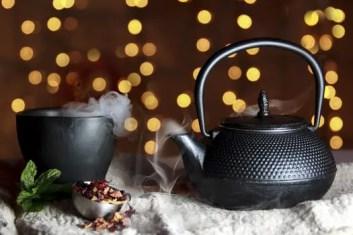 Japanese metal tea kettle and steaming mug of scented tea