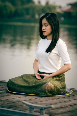 Meditating artist on pier near water