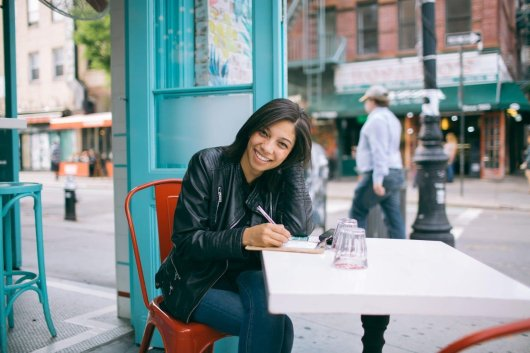 Happy writer at outdoor cafe , no longer plagued by unclear writing!