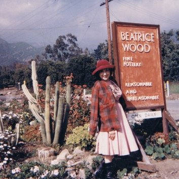 "Beatrice Wood Next to Her Ojai Studio Sign, 1958.   If you look closely you'll see her  sign reads ""Fine Pottery: Reasonable and Unreasonable."""