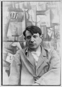Portrait photograph of Pablo Picasso ( who enjoyed a creative rivalry with matisse), in front of his painting The Aficionado (Kunstmuseum Basel) at Villa les Clochettes, Sorgues, France, summer 1912