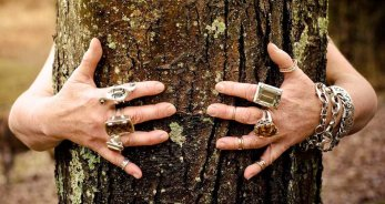 """Treehugger,"" Klar's hands, loving a tree with various bracelets and rings. Copyright ©2015 <a href=""http://www.clearmetals.com"">Barbara Klar</a>. Used by permission of the artist. photo by Franco Vogt. Used as banner image."
