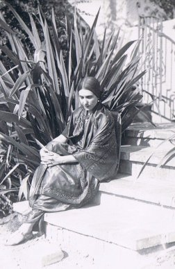 Black and white photo of a Beatrice in a a sari, seated on a California staircase with negation in background.