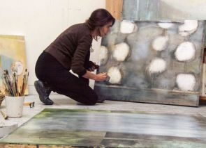 Artist painting in her studio, for writing coaching for artists page