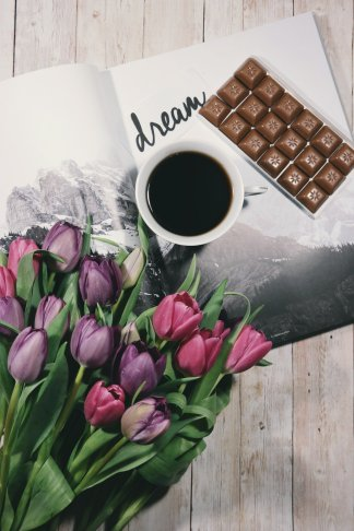 Tulips, coffee, chocolate and an open magazine with the word dream