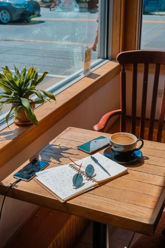 Beautiful sun shining on a coffee shop table where a writer has been working
