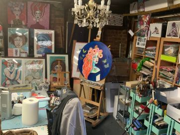 A photo of an artist's charmed studio in her garage, About page