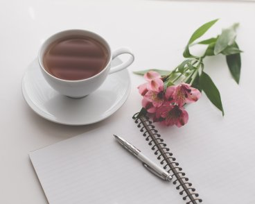 tea cup, flowers and open notebook with pen image for art newsletter post