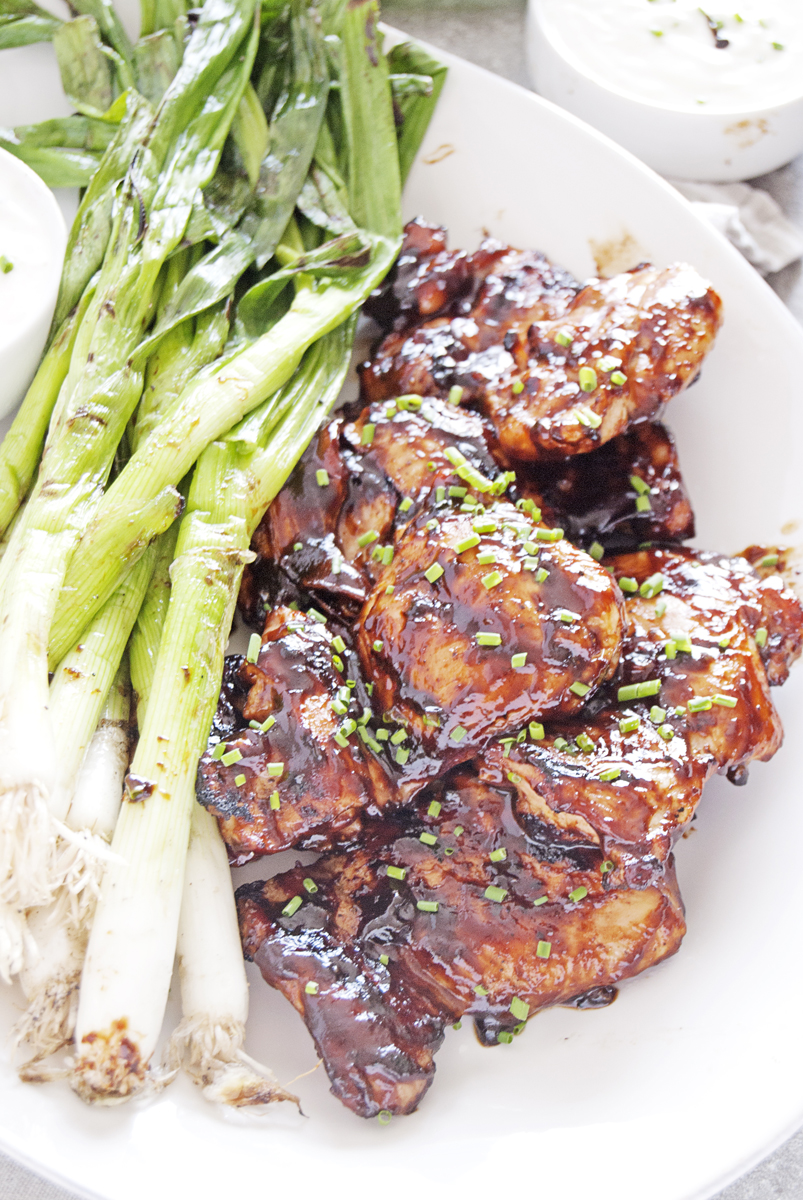 These grilled BBQ chicken thighs are an easy weeknight meal that packs a huge flavor punch when combined with charred scallions and Greek yogurt sauce!