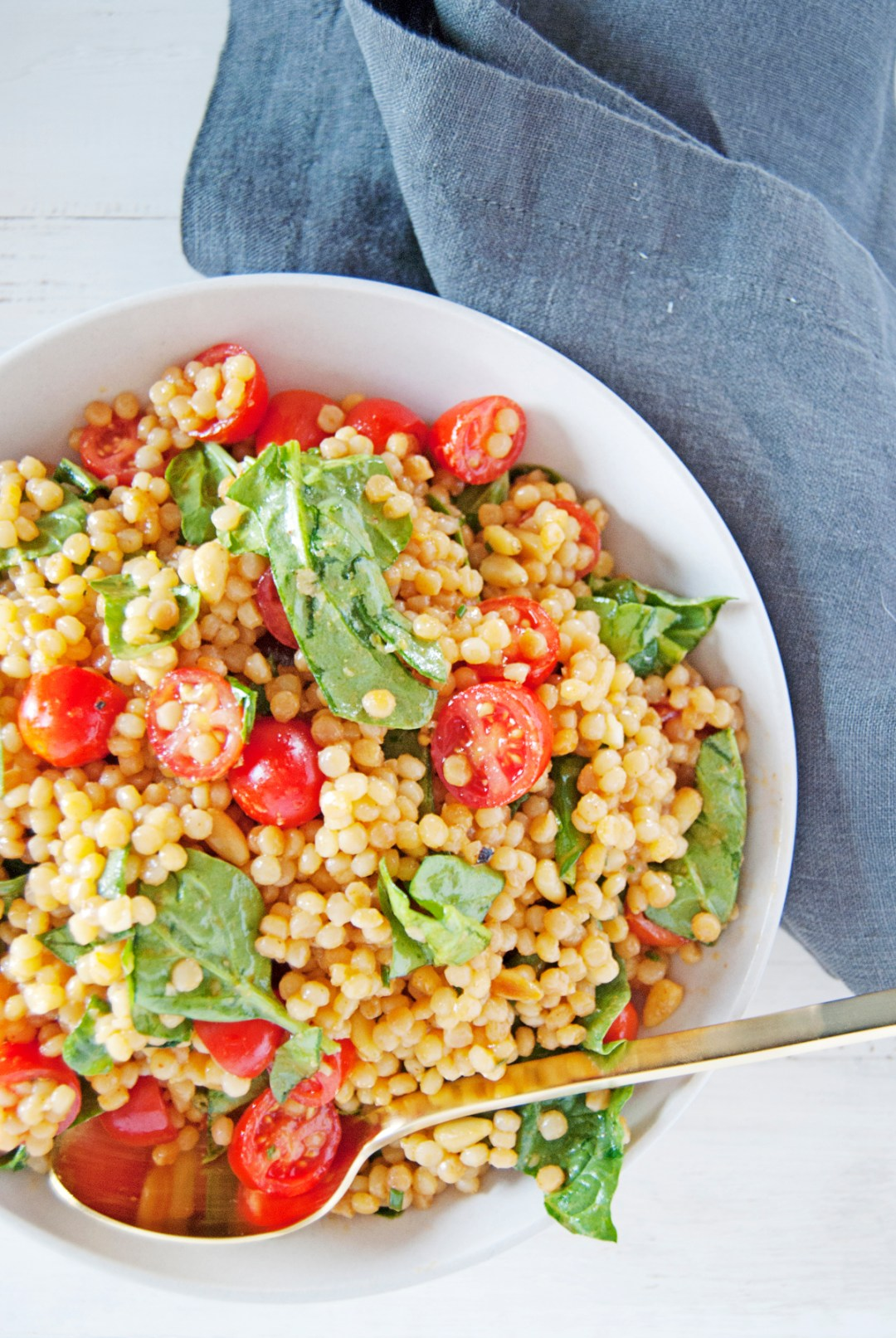 This toasted pearl couscous salad is cooked with paprika and features a refreshing lemon and Dijon mustard vinaigrette, cherry tomatoes, and spinach.