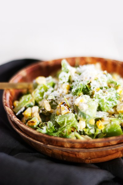 This refreshing roasted corn summer salad featured charred corn, grilled green peppers, and tons of fresh herbs and cheese all mixed together with a tangy Greek yogurt dressing.