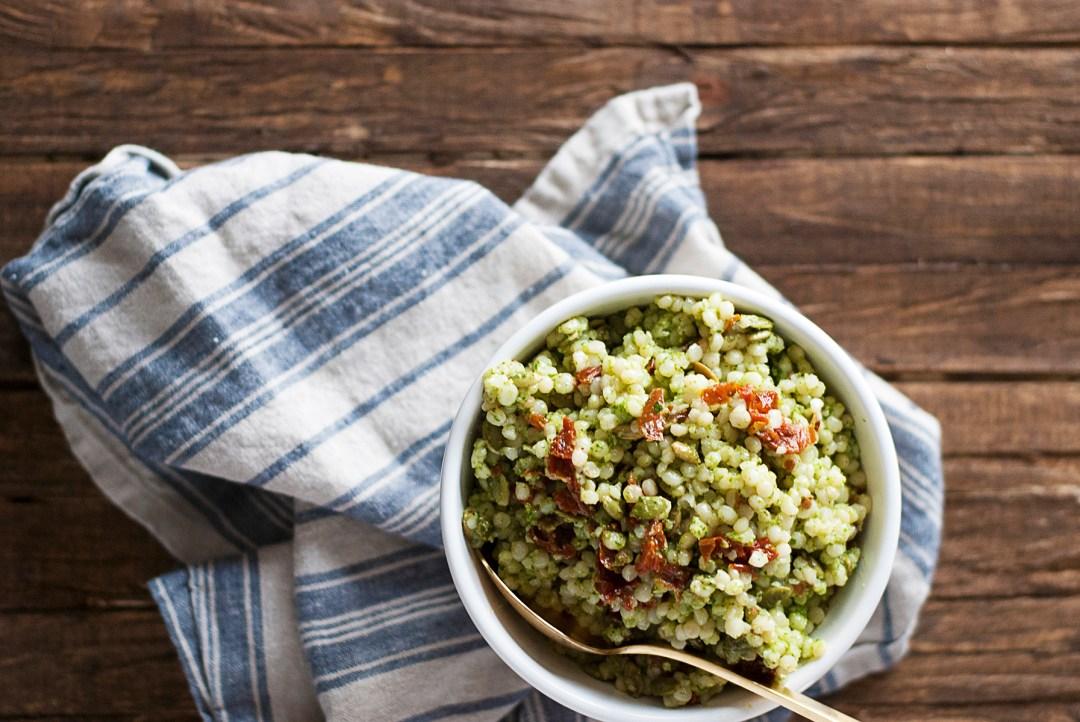A quick arugula pesto couscous salad featuring Israeli couscous, fresh arugula pesto, toasted pepitas, and sun-dried tomatoes.