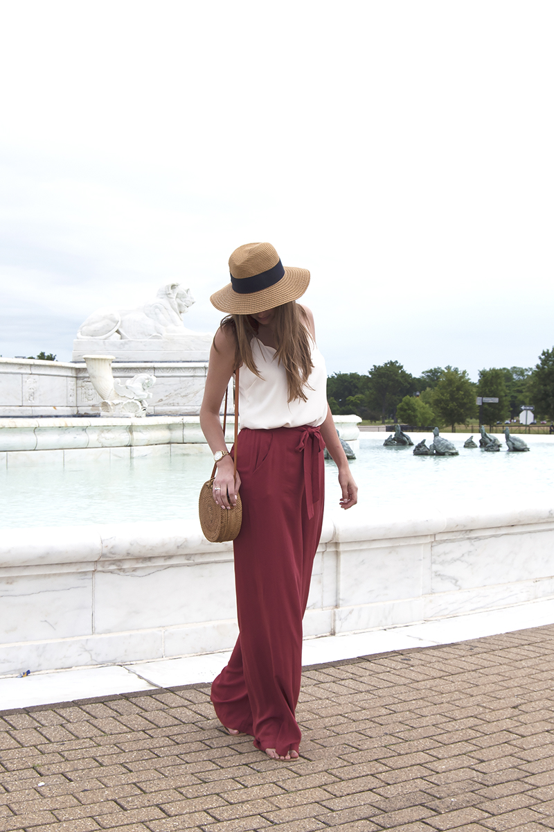 Rusty red wide-legged pants paired with a white blouse and straw hat make for a perfectly relaxed yet sophisticated Fourth of July outfit, plus be sure to read to the end of the post to catch some other cute Fourth of July outfit ideas!