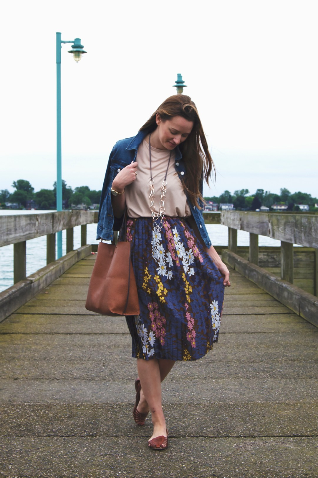 A gorgeous pastel summer floral skirt is paired with a blush pink blouse, jean jacket, and my favorite leather summer sandal of all-time in this summer work outfit!