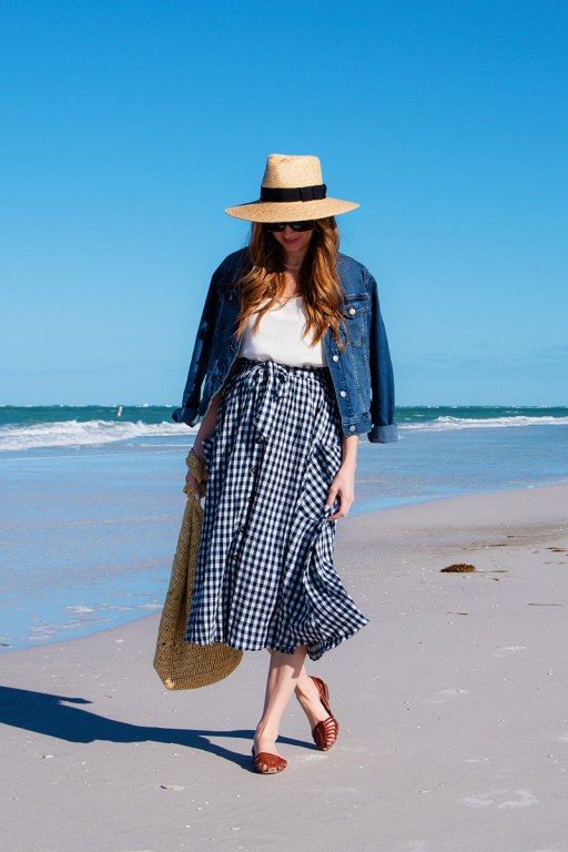 This navy gingham midi skirt is the perfect spring-to-summer transition piece, and is paired with a white blouse and jean jacket for a casual spring look.