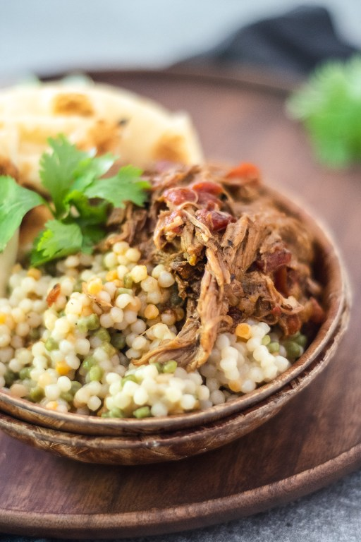 This shredded instant pot Moroccan pork stew is fork tender and falling off the bone, and pairs perfectly with fluffy couscous and toasted naan bread!