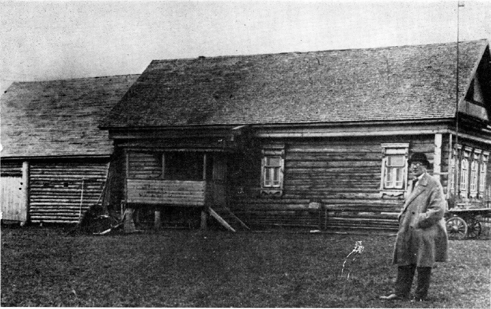 Le Corbusier standing in front of a traditional wooden Russian peasant house (1928)