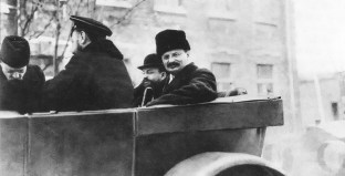 Trotsky rides in the back of a motorcar in Petrograd, 1918