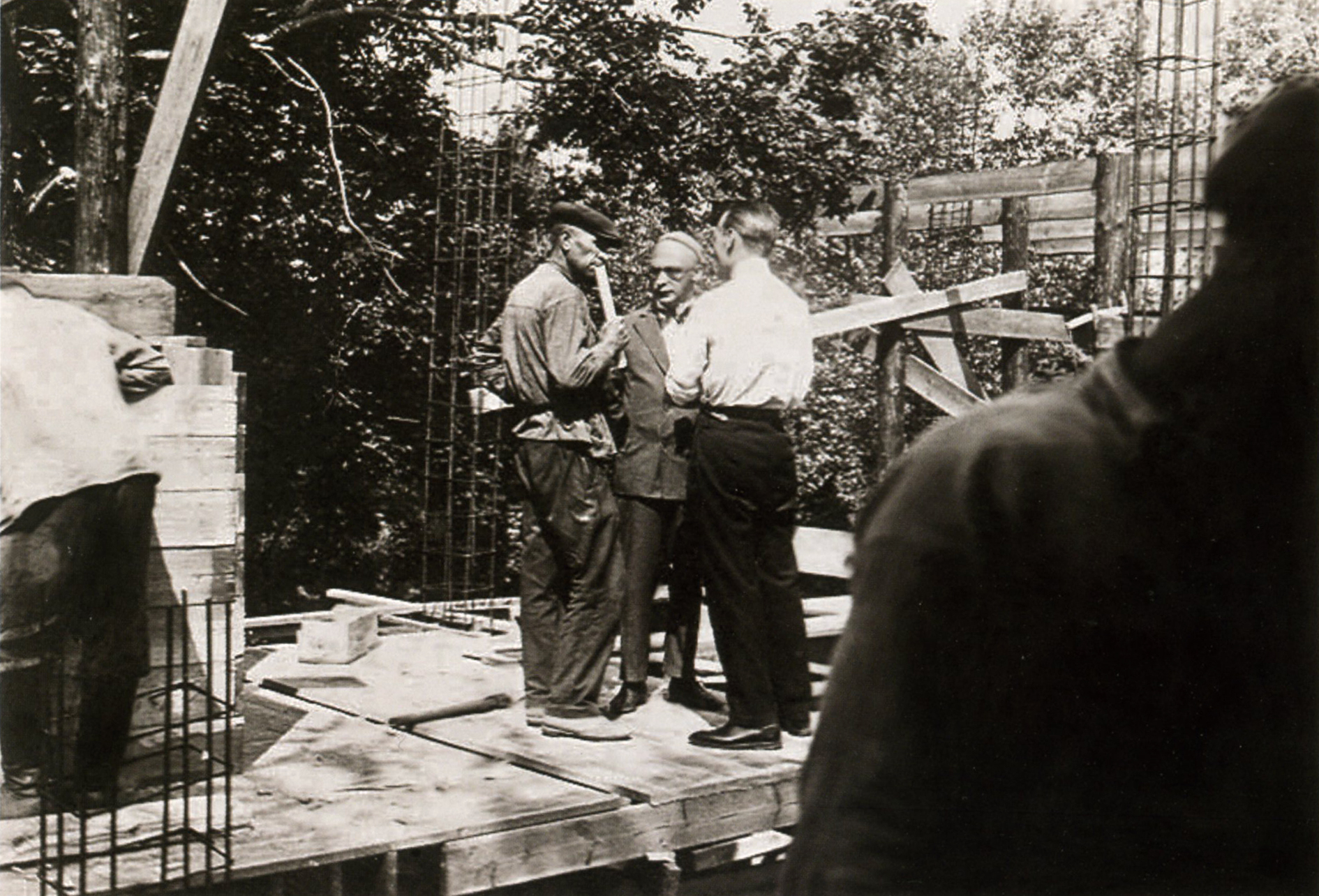Moisei Ginzburg surveys the site with construction workers, 1929