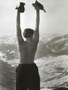 Charlotte Perriand standing shirtless and triumphant overlooking the Swiss Alps, 1935