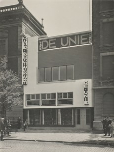 View of Cafe de Unie in Rotterdam, designed by the architect J.J.P Oud. Several groups stand at sides of image looking towards the photographer, 1933