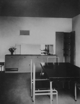 Unknown Interior view of the dining room of House 8 showing a table, chairs, buffet and serving window open to the kitchen, Weissenhofsiedlung, Stuttgart, Germany 1927 or later