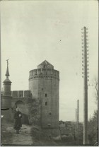 Margaret Bourke-White, Russian peasant woman standing on path in front of castle-like tower & wall fortification near tall poles studded w. strange insulators which 24 separate lines (Kolomna, 1931)