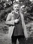 Hendrik de Man met pijp poserend in een tuin. Jaren 1920