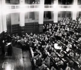 Hendrik de Man op het spreekgestoelte en het publiek bij een voordracht in Duitsland, 1952