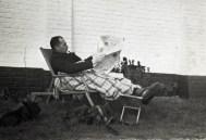 Zwart-witfoto van Hendrik de Man in een ligzetel in de tuin met 2 honden. Jaren 1930