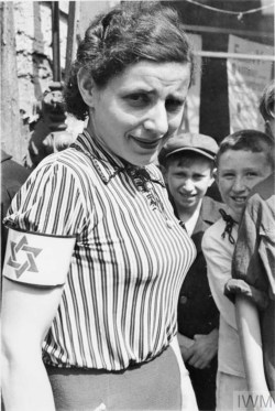 A portrait of a young woman wearing a striped blouse and an armband with the Star of David