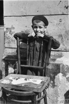 A young boy selling a handful of sweets from a chair in the street