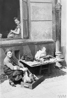 An elderly Jewish woman selling her scarce possessions in the street of the ghetto