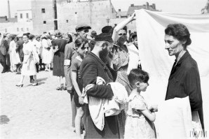 Ghetto residents buying and selling bedsheets in a street market