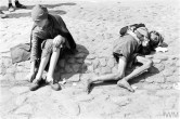 Two emaciated children, one of them asleep or unconscious, begging on the street of the ghetto