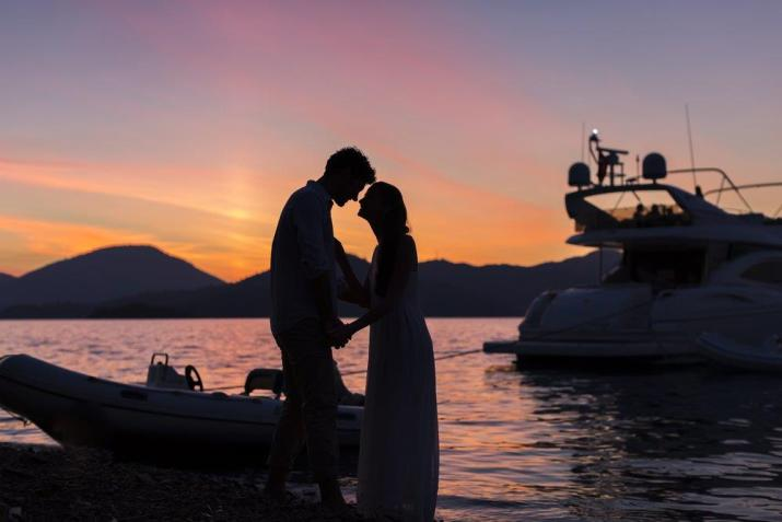 Couple romantic sunset at waters edge close to motor yacht enjoying romance