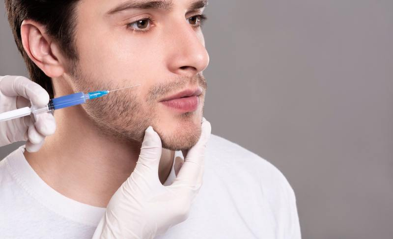 Confident young man having filler injection in his cheek-bone