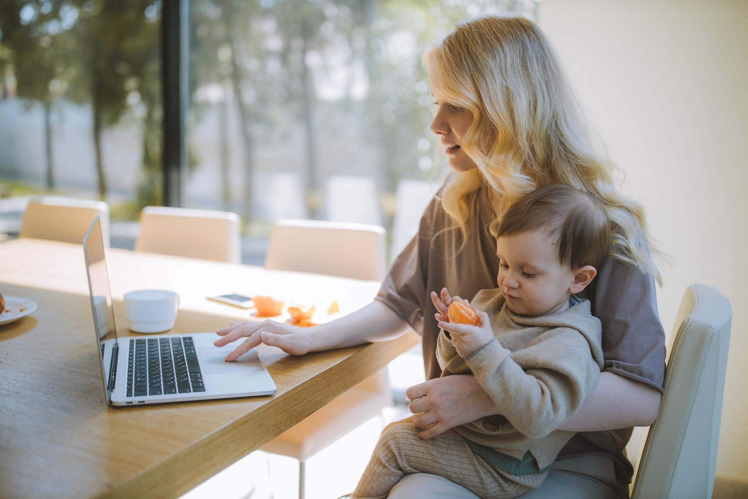 woman holding kid while on laptop