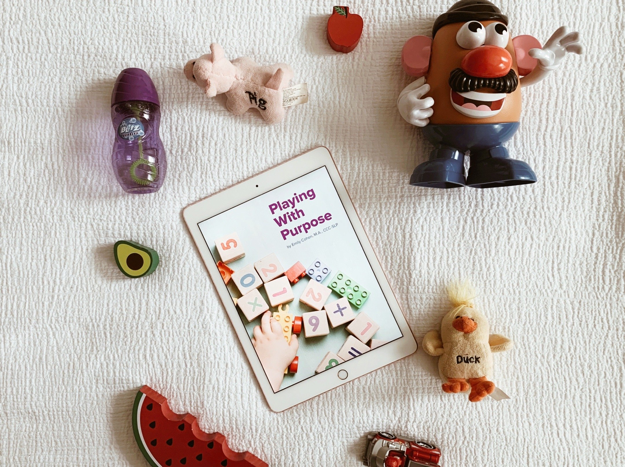 toys and ipad on bed