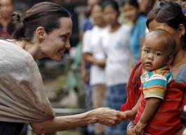 UNHCR special envoy Angelina Jolie Pitt shakes hand with Kachin ethnic refugee kid as she visits Jam Mai Kaung IDP camp in Myitkyina capital city of Kachin state, Myanmar, July 30, 2015. REUTERS/Soe Zeya Tun