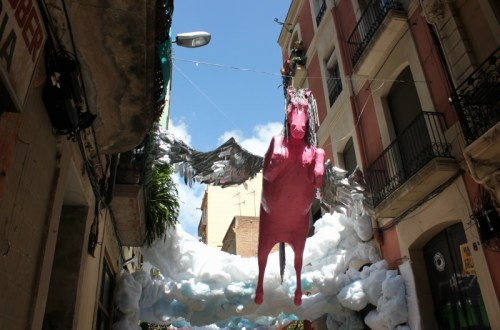 pink pegasus emerges from clouds over street