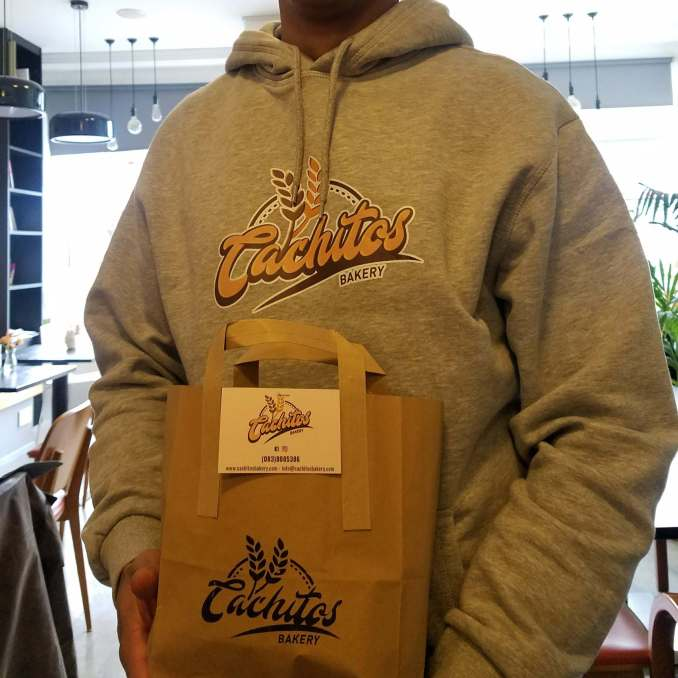 Photo of Rafael Plaza, entrepreneur and owner of Cachitos Bakery, holding a Logo bag