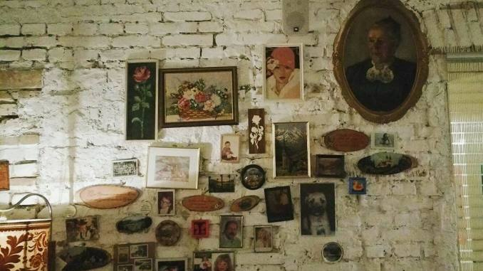Portraits and paintings on a white brick wall