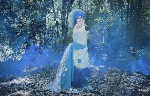 Women in blue dress in a forrest with blue smoke surrounding her