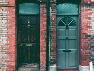 brown wooden door on red brick wall