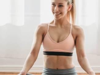 athletic woman smiling while sitting in half lotus pose on mat
