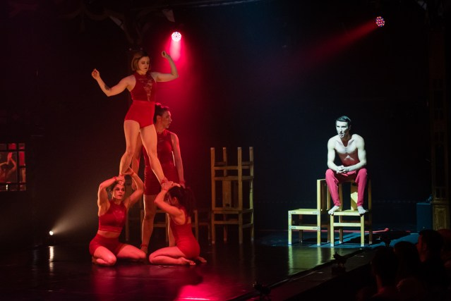 To the lefthand side a woman in red underwear stood on the heads of 2 other women who are on their knees to the right a man in red trousers and no top sits on the back of a chair.