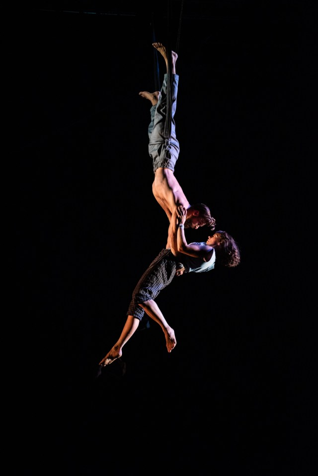 A man hanging upside down holding a woman around her waist hanging underneath him. All in a black background