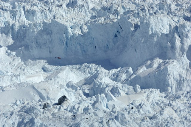 A helicopter flies past a section of the face of a glacier in Greenland.