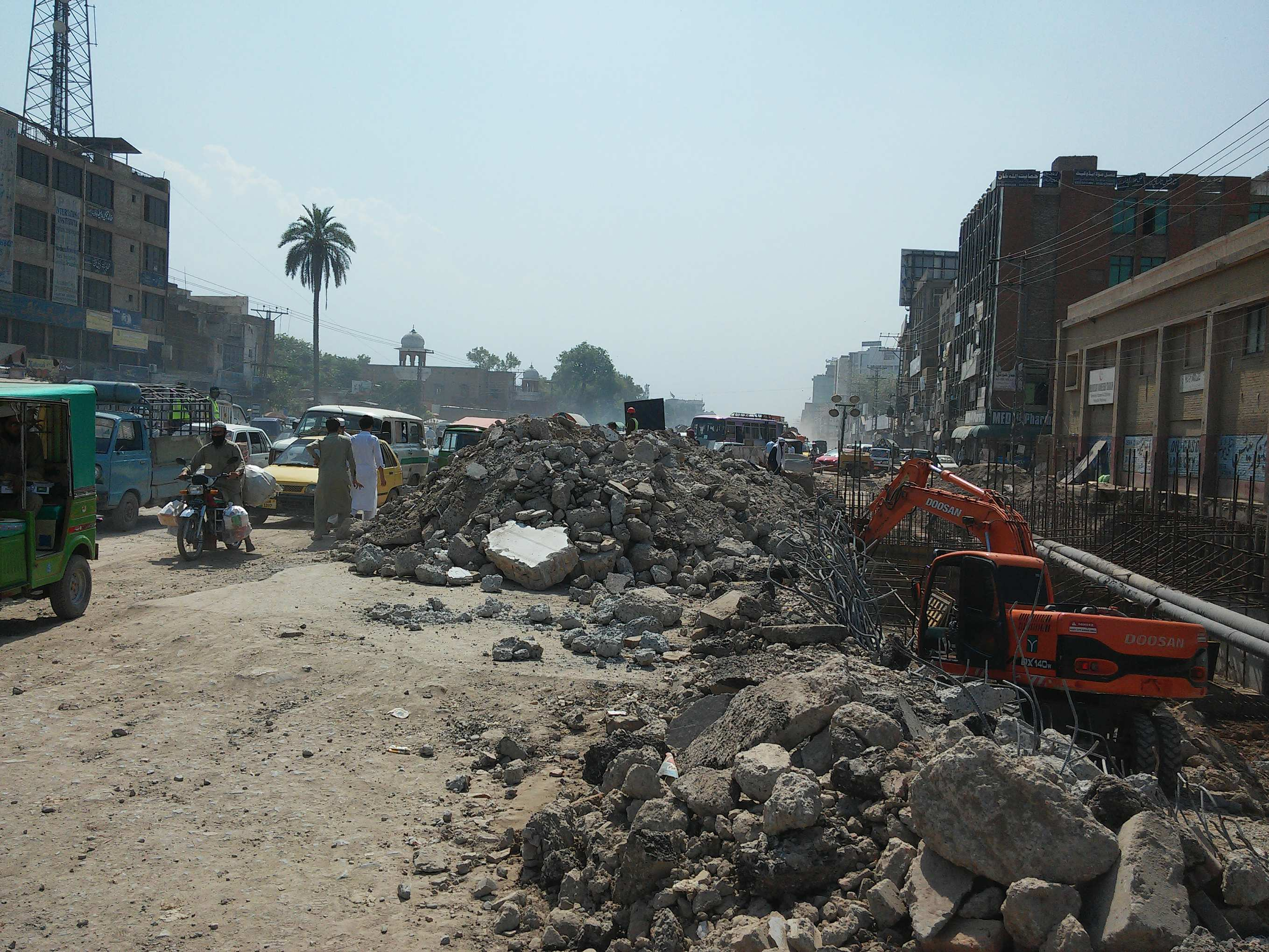 Motorist traveling along a poorly maintained road, exposed to building rubble, construction materials and machinery.